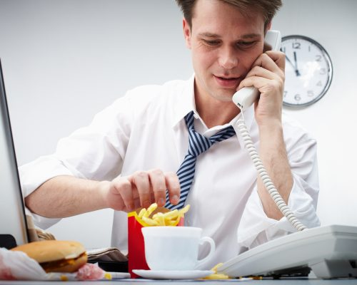 Portrait of modern businessman speaking by the phone while eating fries potato