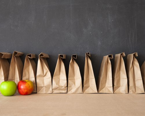 A row of brown bags against a blackboard.