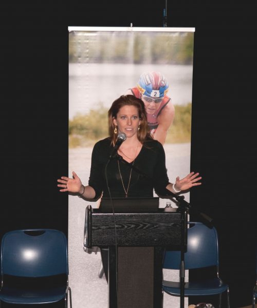 jaime Windrow speaking at Columbia University in front of athletic backdrop