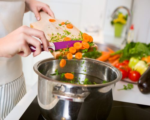 Fresh vegetables on the cutting board are falling in the pot, concept of cooking